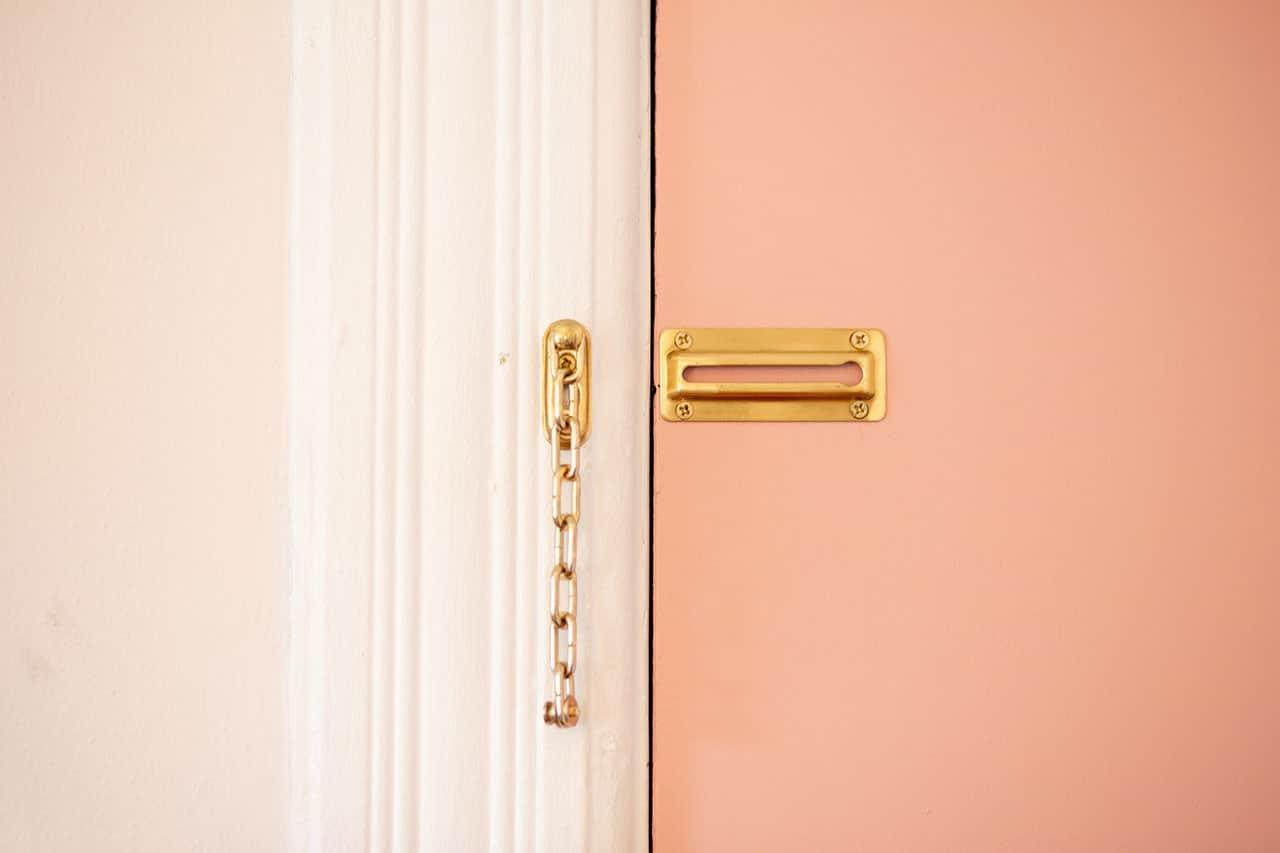 Oranssi ovi, jonka kultainen varmuusketju on auki.