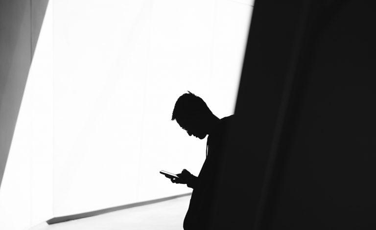 Varjokuva miehestä, jonka katse on tiiviisti puhelimessa kiinni.