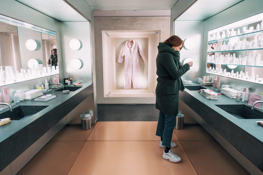 Nainen tutkii meikkejä New Yorkin Glossier meikkikaupassa.