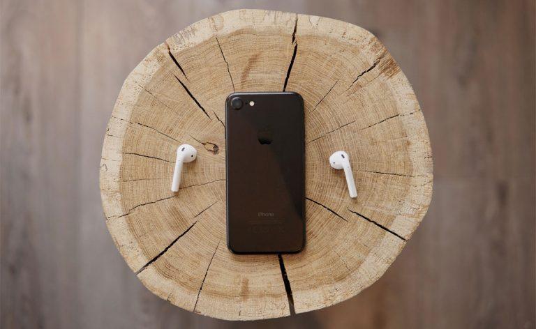 Puhelin ja langattomat kuulokkeet on asetettu puupölkyn päälle.