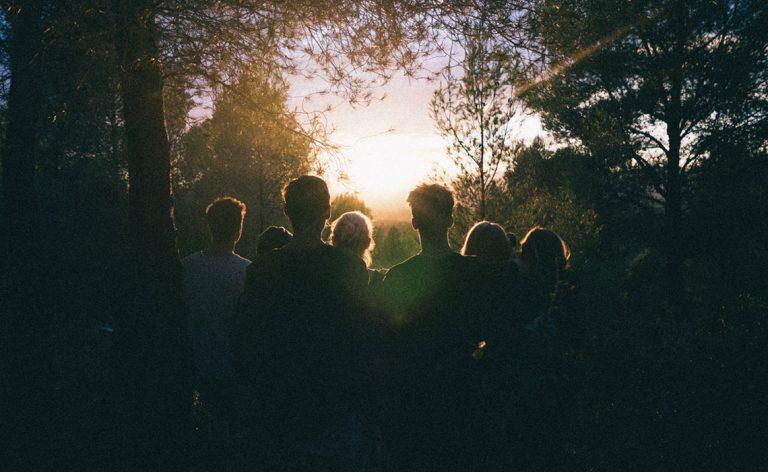 Ryhmä ihmisiä katsoo kohti nousevaa aurinkoa pimeän metsän siimeksestä.