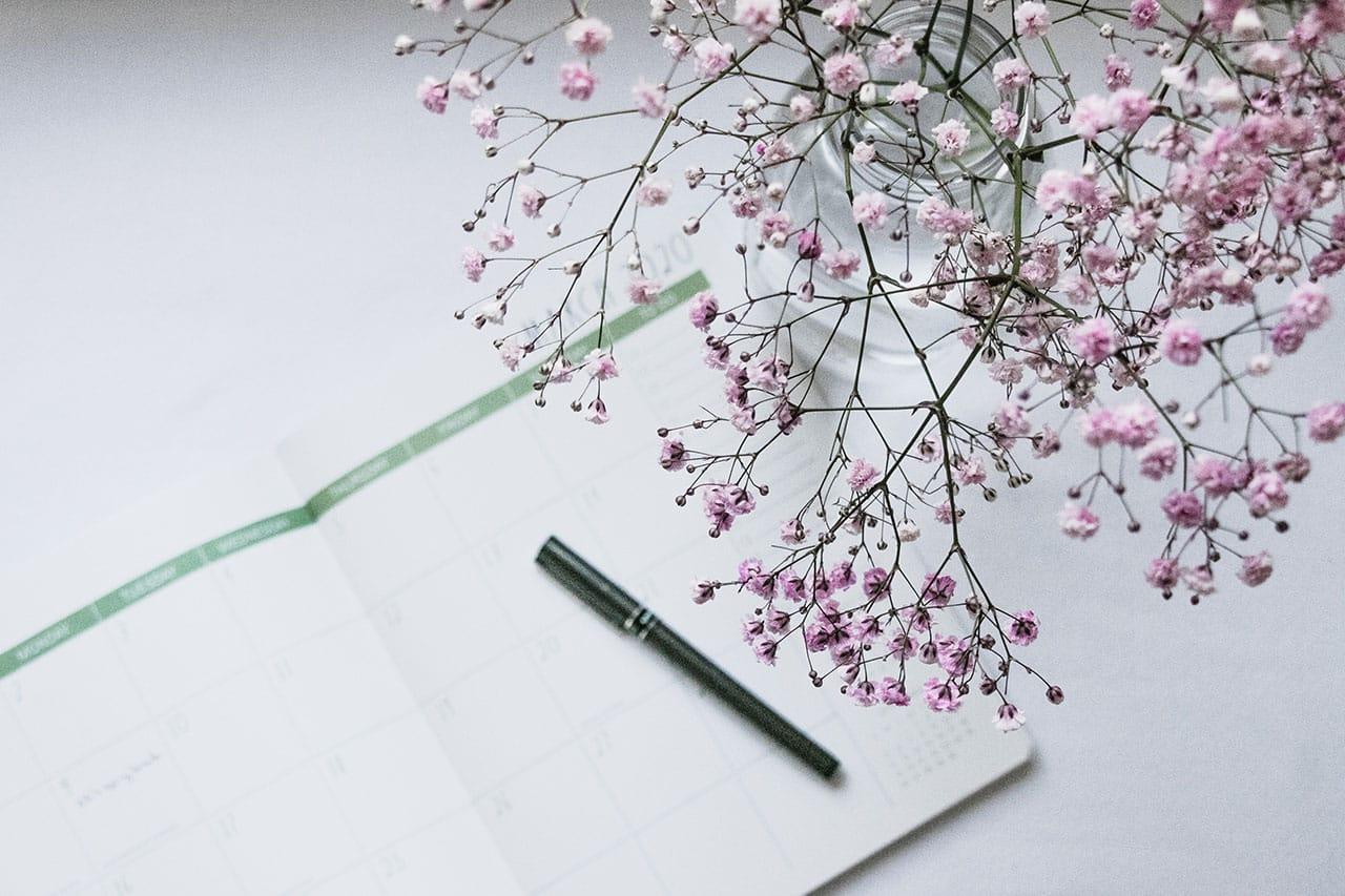 Aukinainen kalenteri, jonka päällä kynä ja vieressä vaaleanpunaisia kukkia.
