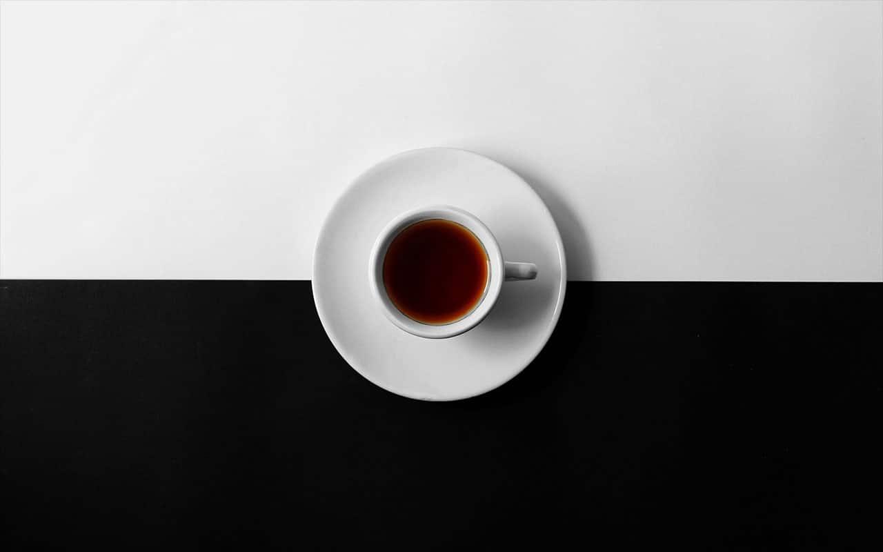 Kahvikuppi kuvattuna ylhäältä mustavalkoisessa taustassa.