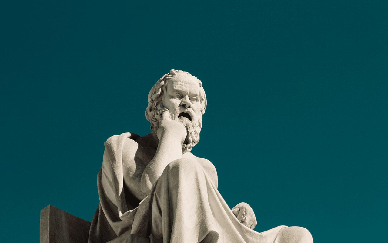 Socrates-patsas, joka nojaa käteensä mietteliäänä.