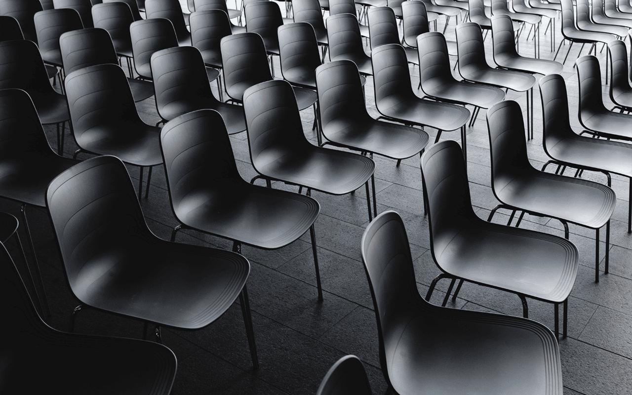 Tyhjät tuolit rivissä kuin etäesiintymisen mustat ruudut.