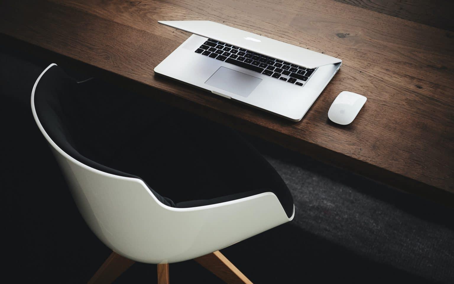 Kannettava tietokone ja hiiri pöydällä